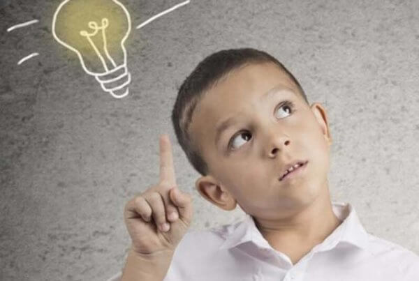 Young boy standing next to a sketched version of Maslow's Hierarchy, and pointing to a sketched lightbulb.